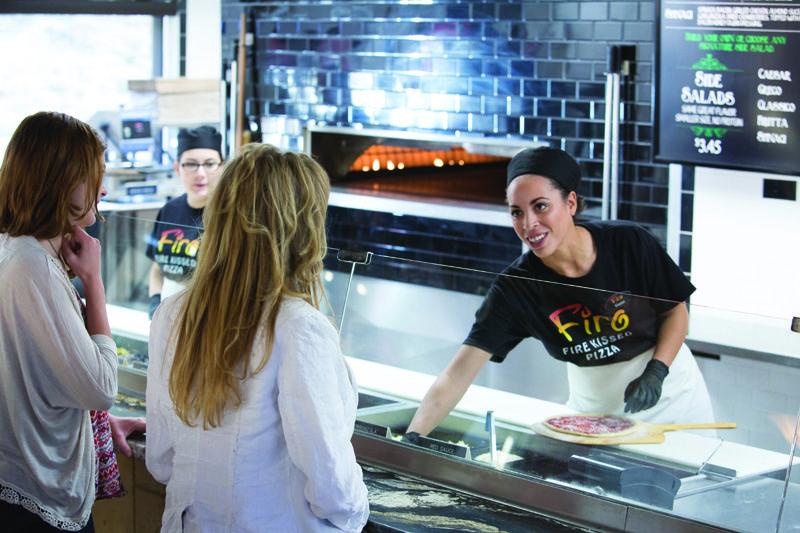 A Firo-ista helping a customer, as she prepares a pizza