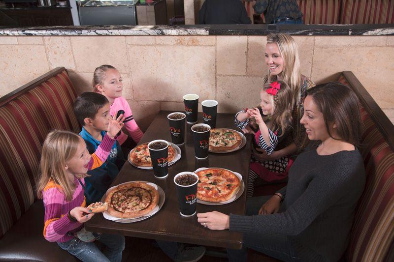 A family sitting at their table enjoying their Firo Pizzas
